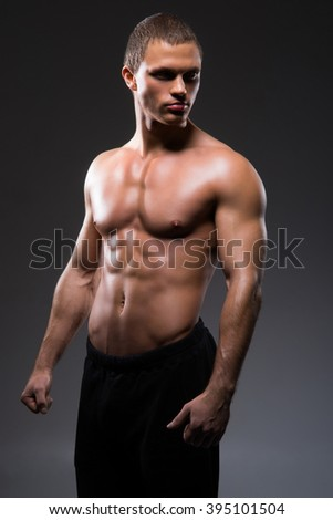 Strong, fit and sporty bodybuilder man over black background - stock photo