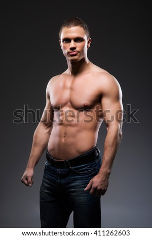 Strong, fit and sporty bodybuilder man over black background