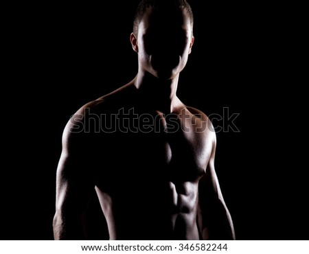 Strong, fit and sporty bodybuilder man shaded over black background