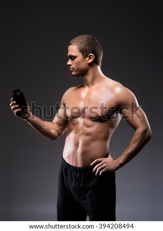 Strong, fit and sporty bodybuilder man with a bottle of sport supplements over black background.