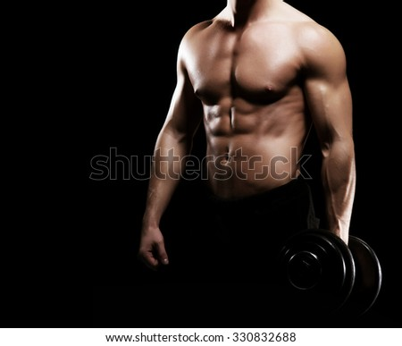 Strong, fit and sporty bodybuilder man with a dumbbell over black background. - stock photo