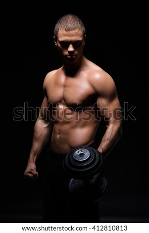 Strong, fit and sporty bodybuilder man with a dumbbell over black background