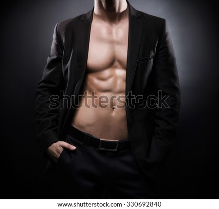 Strong, fit and sporty stripper man over black background. - stock photo