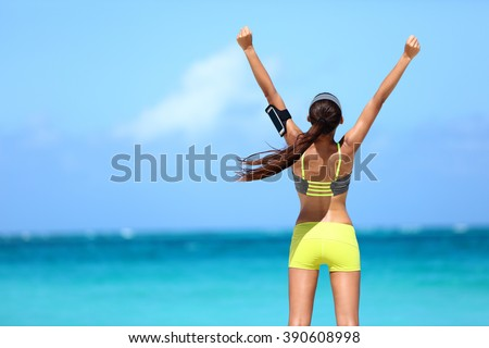 Strong fitness athlete arms up in success on summer beach after cardio training workout. Female runner woman running winning reaching goal achievement during strength training showing power. - stock photo