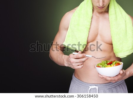 Strong fitness man holding a bowl of fresh salad on dark background - stock photo