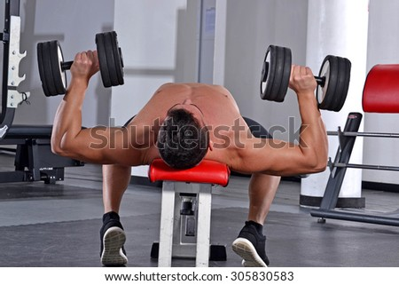 Strong fitness sport man training with gym weights.Athletic young man laid on back working his chest with heavy dumbbells
