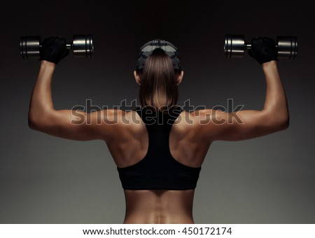 Strong fitness woman bodybuilder with tanned body pumps up the muscles lifting dumbbells. - stock photo