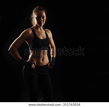 Strong fitness woman on black background, low key lighting - stock photo