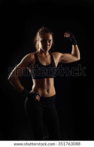 Strong fitness woman on black background, low key lighting