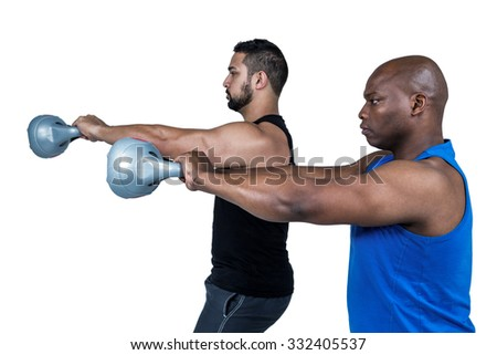 Strong friends lifting kettlebells together on white background