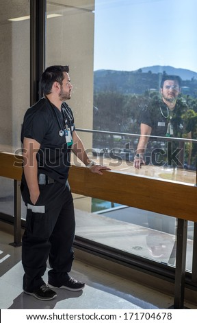 Strong good looking health care worker standing next to a large window with his reflection in the glass - stock photo