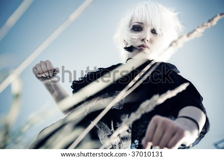 Strong goth woman portrait camera view from the ground. - stock photo