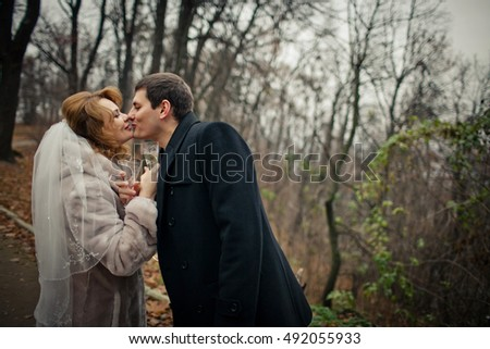 Strong groom kisses bride tender while they drink champagne in autumn park