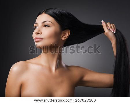 Strong hair. Beautiful young shirtless woman holding her hair in hand and looking away while standing against grey background   - stock photo
