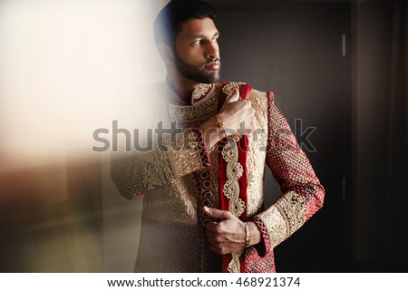 Strong handsome Indian groom holds his hands over wedding suit
