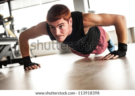 Strong, handsome man doing push-ups in a gym as bodybuilding exercise, training his muscles - stock photo