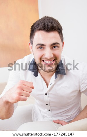 strong handsome man laughing and showing his fist