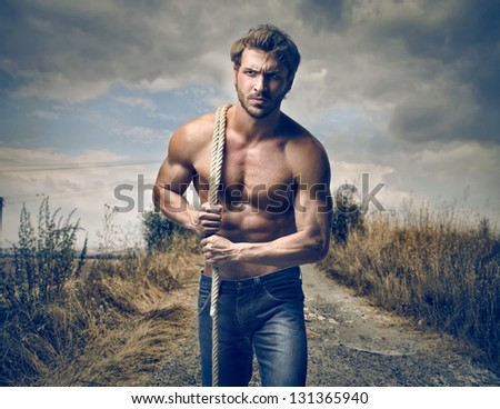 strong handsome man with rope - stock photo