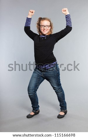 Strong happy funny teenage girl with curly blonde hair. Power. Wearing glasses. Expressive face. Studio shot isolated on grey background. - stock photo