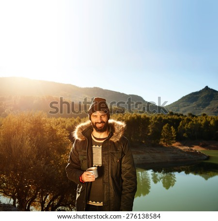 Strong hiker standing on the mountain near lake in background and resting with hot coffee. Happy multiracial smiling man outdoors. Lifestyle photo of Caucasian breaded man.    - stock photo