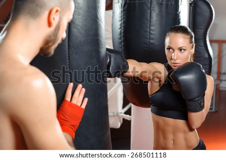 Strong jab. Young beautiful woman boxer kicking a punching bag with a jab - stock photo
