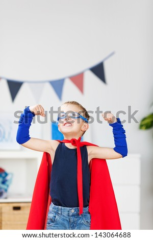 Strong kid wearing a superhero costume and showing his muscle - stock photo
