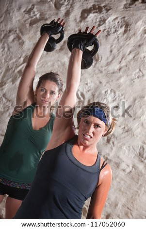 Strong ladies pushing up kettle bell weights during boot camp workout - stock photo
