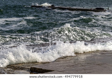 Strong large sea wave during a sea storm. Seascape with storm surge and sea spray on an empty city beach for swimming holiday travelers