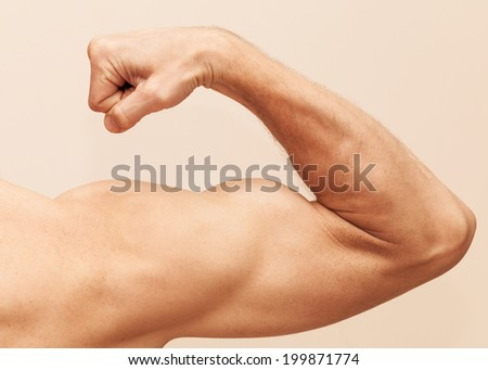 Strong male arm shows biceps. Close up photo - stock photo