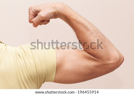 Strong male arm shows biceps. Closeup photo - stock photo