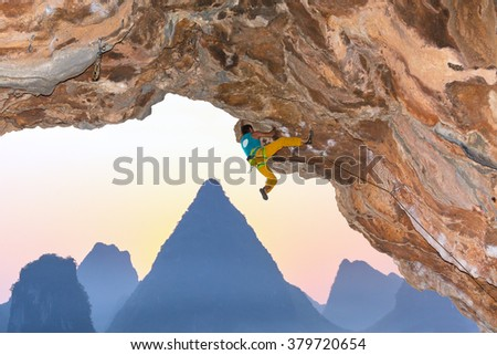 Strong Male Rock Climber ascending dangerous rocky Roof Mountains in China on Luminous Sunrise Background