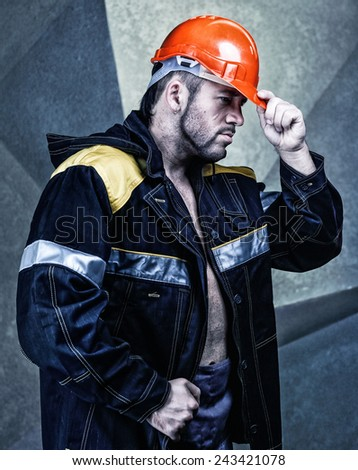 Strong male worker in the helmet and workwear - stock photo
