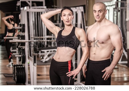 Strong man and a woman posing in a gym   - stock photo