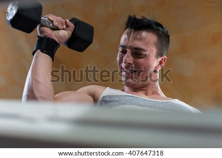 Strong man at the gym lifting heavy weights - stock photo