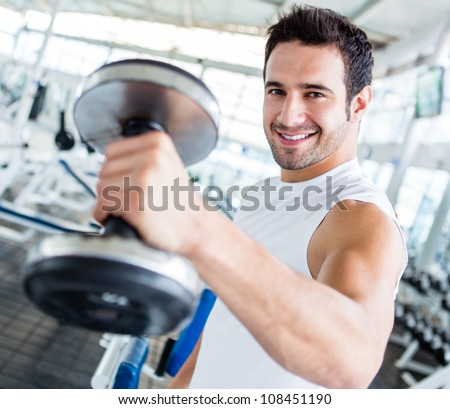Strong man at the gym lifting weights - stock photo