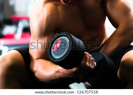 Strong man, bodybuilder exercising with dumbbells in a gym - stock photo