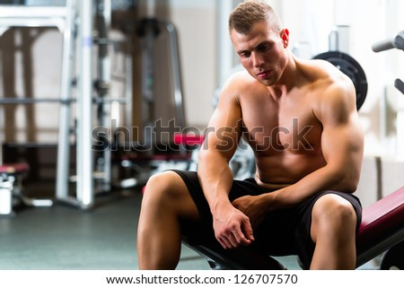 Strong man, Bodybuilder sits on a weight bench in a gym, he takes a break - stock photo