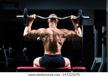 Strong man - bodybuilder with dumbbells in a gym, exercising with a dumbbell - stock photo