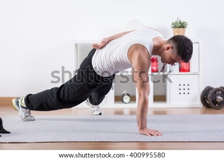 Strong man doing push-ups on one hand - stock photo