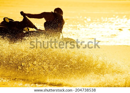 strong man drive on the jet ski above the water at sunset .silhouette. spray. - stock photo