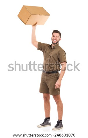 Strong man. Happy delivery man standing and holding carton box in raised hand. Full length studio shot isolated on white. - stock photo