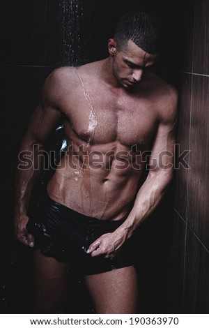 Strong man in chains posing under the rain, aqua studio .Glamour colors. .Shallow depth of field with focus on abdominals. Fine art.
