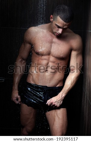 Strong man in chains posing under the rain, aqua studio .Low light .Shallow depth of field with focus on abdominals.
