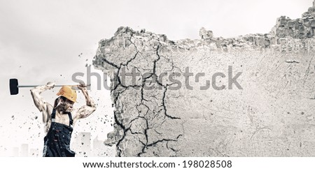 Strong man in uniform breaking brick wall with hammer - stock photo