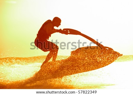 strong man jumps on the jetski above the water at sunset .silluet. spray. - stock photo