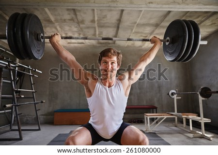 Strong man lifting heavy training weigths looking determinedly in front of him