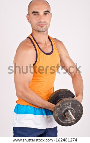 Strong man lifting weights. Bodybuilder training hard with heavy dumbbells.