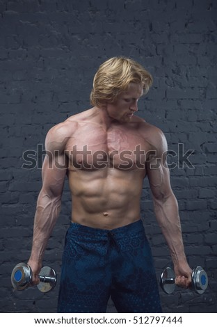 Strong man. Muscular bodybuilder doing exercises with dumbbells over brick wall background.