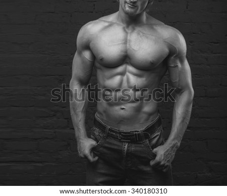 Strong man. Muscular male body. Bodybuilder. Black and white image. Copy space for text. Posters, advertising for gym. Muscular man on dark background brick wall. Athletic man. Fitness muscular body.