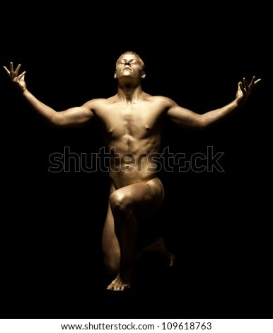 Strong man posing nude in dark with gold skin